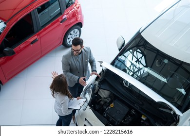 Top view of car salesman and buyer discussing about vehicle. Standing by new car with opened hood.