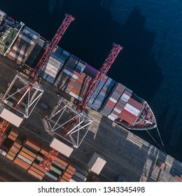 Top view of a cargo ship with containers, which is unloaded in the port. Container Warehouse, Logistics, Cranes, Outdoor, Import and export. Top view