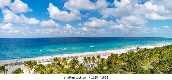 Top view of the Caribbean dream beach in Varadero Cuba with sun lounger and thatched huts. Panoramic view of the 20 km long beach of the resort town of Varadero.