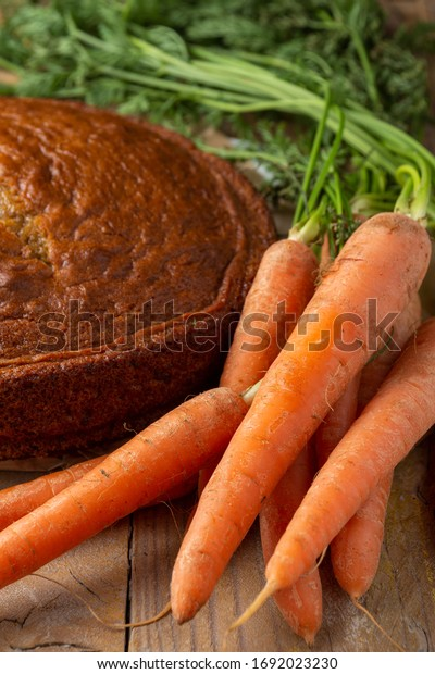 Top view of carrots with leaves and sponge cake, on rustic wooden table, vertical