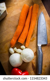 Top view of carrots, onions and a knife