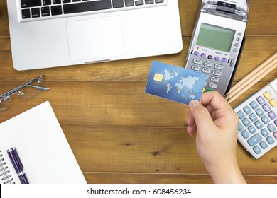 Top view of cashier hand holding a Credit card over EDC machine or credit card terminal with calculator and glasses. This is fake credit card.
