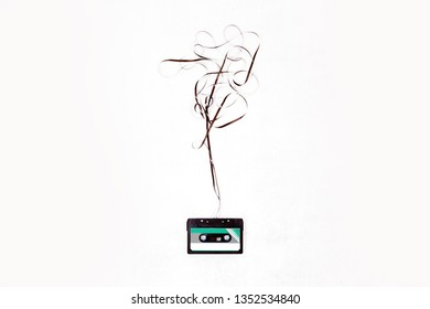 Top view cassette tape over white background with tangled ribbon.