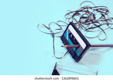 Top view cassette tape over white background with tangled ribbon with pencil to rewind