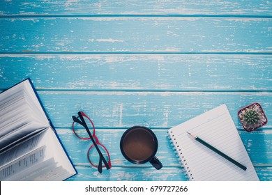 Top view casual lifestyle of work accessories on the vintage blue wood background, book, coffee, paper, glasses, pen and items objects on wooden, with copy space, Working desk table concept.
