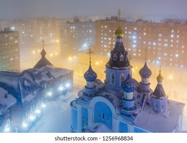 Top view of the Cathedral in Norilsk. Snowfall and foggy mist on a cold winter evening in the arctic. Colorful street lighting of a large northern city. Krasnoyarsk region, Siberia, Russia.