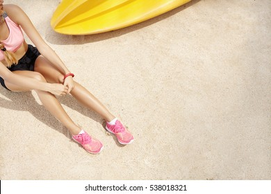 Top view of Caucasian woman runner in sportswear sitting on beach after active training at seaside. Sportswoman in pink running shoes catching her breath while resting on sand during workout