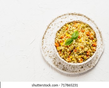 Top view of cauliflower rice with vegetables. Organic paleo Cauliflower Rice with corn, green peas and carrots on white concrete background. Copy space.