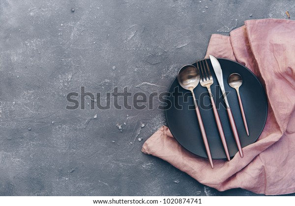 Top view of ceramic plates on linen and rustic silverware on blue shabby chic surface