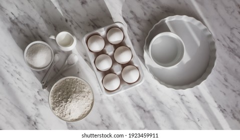 Top view ceramic tray with eggs placed near bowl of flour and sugar. White utensils with white ingredients on white surface. Copy space.