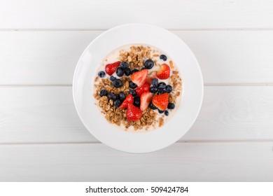 top view of cereal muesli breakfast with yogurt and fresh berries