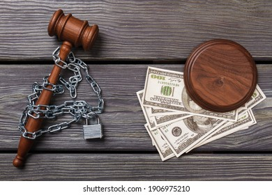 Top view chained gavel and dollars. Concept of bribe and corruption in a court.