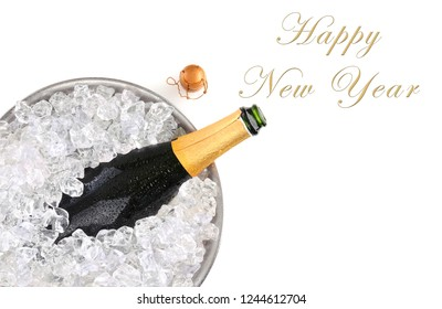 Top view of a champagne bottle in metal ice bucket with the words Happy New Year with room for your copy.
