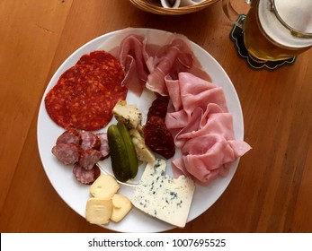 Top view of a charcuterie plate and glass of beer on a wooden table. Appetizer plate of cheese, cured meats, and pickles. Looking down on meet and cheese plate and local pub in Prague.