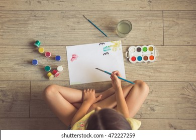 Top view of charming little girl painting using watercolors and gouache while sitting on the floor in her room at home