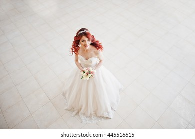 Top view of charming red-haired bride with wedding bouquet at hand posed against wgite tile on the great wedding hall