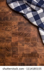 Top  of view checkered tablecloth on empty wooden butcher board.