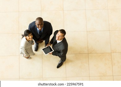 top view of cheerful business team using tablet computer
