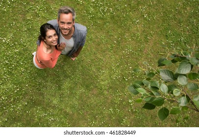 Top view. cheerful couple, standing barefoot in the grass looking at the camera.  The man has grey hair