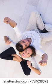 top view of Cheerful young couple sitting with back to each other on floor