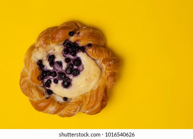 Top view of cheese danish puff pastry with blackberries and vanilla custard on punchy yellow background with room for copy space
