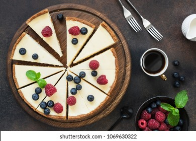 Top view of cheesecake with summer berries on dark background. Horizontal composition