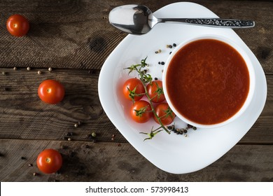Top view of cherry tomato soup on a wooden background