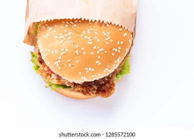 Top view chicken burger in paper bag package on white background and copy space.Fast food for breakfast.Junk food or unhealthy food concept.