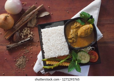 top view of a chicken curry, is a food made from chicken soaked with herb and spices sauce, presenting with rise, bean sprouts, tomato, cucumber, carot and long beans as vegetable on a white napkin