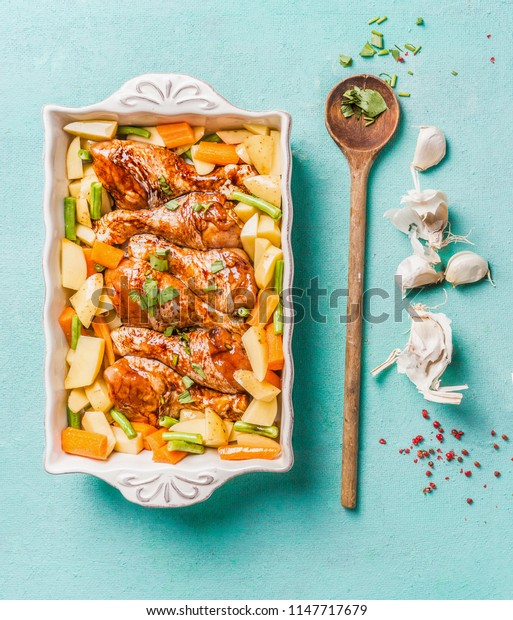 Top view of Chicken drumsticks with vegetables in baking casserole on light blue background with cooking spoon and seasoning and spices. Healthy food concept