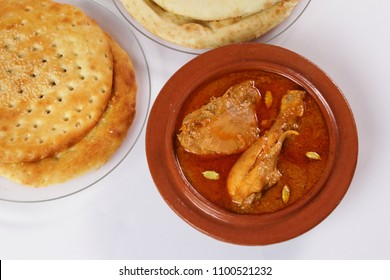 Top view of chicken Qorma with naan and sheermal or taaftan bread.