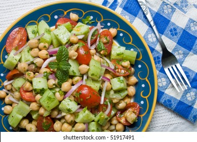 A top view of chickpea (garbanzo bean) salad on a colorful plate