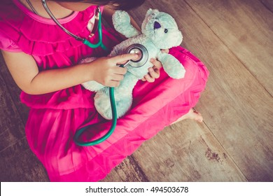 Top view of child playing doctor or nurse with plush toy bear with bright sunlight at home. Happy girl listens a stethoscope to toy. Playful girl role playing. Vintage tone effect.