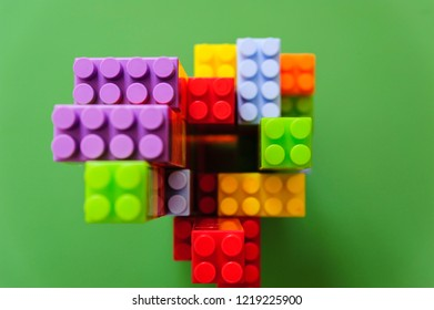 Top view of a children construction made out of colored blocks isolated on a green background.