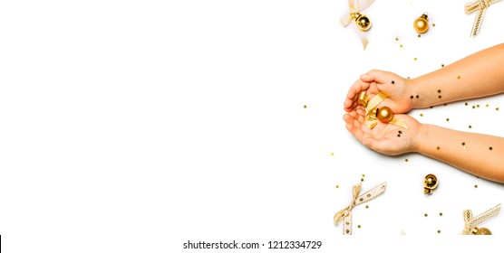 Top view of Children hands holding christmas ball and other decorations in golden colors isolated on white. Flat lay and empty copy space for text. Bright and festive celebration or greeting card.