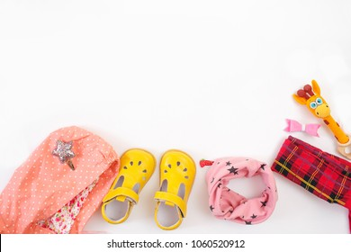 Top view of children's fashion clothes: accessories on a white wooden background