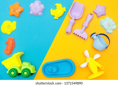 top view of the children's play set for sand, playing in the sandbox, at sea or in the park. Bright plastic, silicone toy set for kids. Flatlay with space for text on a bright yellow-blue background