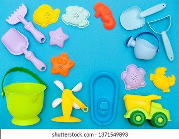 top view of the children's play set for sand, playing in the sandbox, at sea or in the park. Bright plastic, silicone toy set for kids. Flatlay on a bright blue background, with space for text
