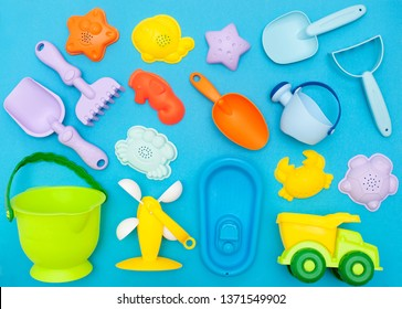 top view of the children's play set for sand, playing in the sandbox, at sea or in the park. Bright plastic, silicone toy set for kids. Flatlay on a bright blue background