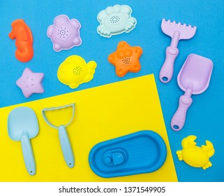 top view of the children's play set for sand, playing in the sandbox, at sea or in the park. Bright plastic silicone toy set for babies: molds for modeling, a boat, a rake and a shove. Summer flatlay