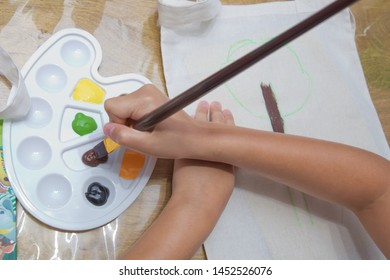 Top view child's hands draws a gouache on paper. Gouache and paper for painting and child drawing. Kid hands painting at the table with art supplies, top view
