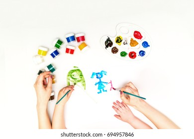 Top view child's hands draws a gouache on paper. Gouache and paper for painting and child drawing family
