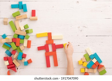 Top view of child's hands playing with colorful wooden bricks on white table background. The cubes lie in the shape of a siren-headed monster. Learning and education concept.