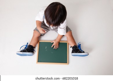 top view of chinese boy writing on the chalk board