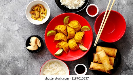 Top view of Chinese food set. Dumplings, boiled rice, spring rolls, fortune cookies on stone table.
