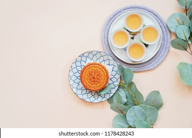 Top view of chinese moon cake with hot tea and green plant on yellow background, holiday and festival concept