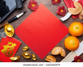 "Top view of Chinese new year decorations with blank red paper as copy space, Chinese calligraphy on red packet ""FU"" (Foreign text means Prosperity)"