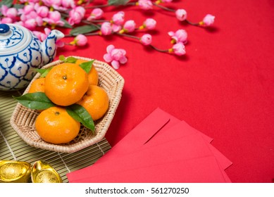 Top view chinese new year accessories Chinese new year festival Orange gold, leaf, wood basket, red packet, Sakura, teapot on red background.