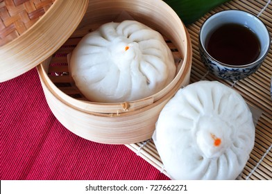 Top view of Chinese pork bun in bamboo container with tea on red mat background