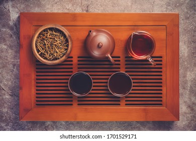 Top view - chinese tea ceremony with clay teapot, clay tea cups, cha hai and wooden bowl.